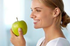 Härlig le kvinna med vita tänder som äter gröna Apple Royaltyfria Foton