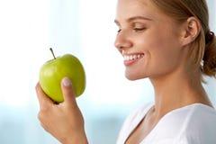 Härlig le kvinna med vita tänder som äter gröna Apple Royaltyfria Bilder
