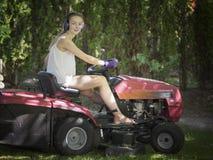 Härlig le kvinna på en ritt på gräsklippningsmaskinen Fotografering för Bildbyråer