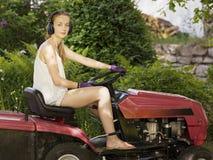 Härlig le kvinna på en ritt på gräsklippningsmaskinen Royaltyfri Foto