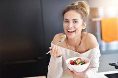 Härlig le kvinna som äter ny organisk vegetarisk sallad i modernt kök arkivbild