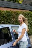 Härlig le kvinna som öppnar en bildörr Arkivfoton