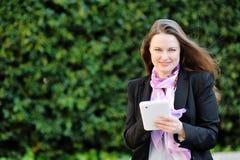 Härlig le kvinna som använder minnestavladatoren Royaltyfri Fotografi