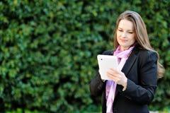 Härlig le kvinna som använder minnestavladatoren Fotografering för Bildbyråer