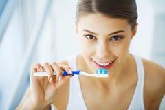 Härlig le kvinna som borstar sunda vita tänder med borsten Royaltyfri Fotografi