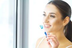 Härlig le kvinna som borstar sunda vita tänder med borsten arkivfoto