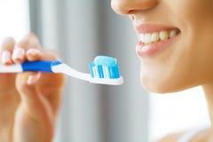 Härlig le kvinna som borstar sunda vita tänder med borsten fotografering för bildbyråer