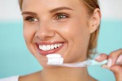 Härlig le kvinna som borstar sunda vita tänder med borsten Royaltyfri Bild