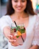 Härlig le kvinna som dricker det kalla lemonadbäret som är utomhus- Arkivfoto