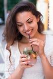 Härlig le kvinna som dricker det kalla lemonadbäret som är utomhus- Arkivbild