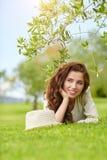 Härlig le kvinna som ligger på ett utomhus- gräs Fotografering för Bildbyråer