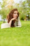 Härlig le kvinna som ligger på ett utomhus- gräs Royaltyfri Bild