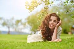 Härlig le kvinna som ligger på ett utomhus- gräs Royaltyfria Foton