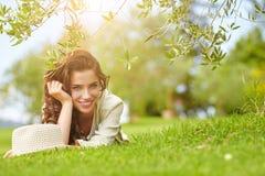 Härlig le kvinna som ligger på ett utomhus- gräs Arkivbild