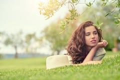 Härlig le kvinna som ligger på ett utomhus- gräs Royaltyfri Fotografi