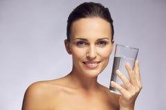 Härlig le kvinna som rymmer ett exponeringsglas av rent vatten Arkivfoto