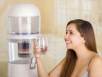 Härlig le kvinna som rymmer ett exponeringsglas av vatten, med ett filtersystem av vattenreningsapparaten på en kökbakgrund royaltyfria foton