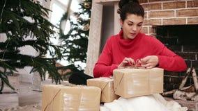 Härlig le kvinna som slår in julklappar som hemma sitter vid julgranen och spisen lager videofilmer