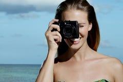 Härlig le kvinna som tar foto på stranden Arkivfoto