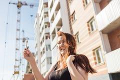 Härlig le kvinna som visar henne nya hem- tangenter mot bakgrunden av ett hus under konstruktion Royaltyfri Foto