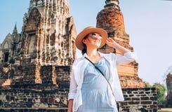 Härlig le kvinnahandelsresandestående på den atcient Wat Chaiwatthanaram Buddhist templet i den heliga staden Ayutthaya, Thailand royaltyfria bilder
