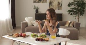 Härlig le kvinnlig för glamour som har frukosten hemma som talar genom att använda smartphonen stock video