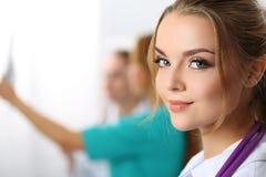 Härlig le kvinnlig medicindoktor som in camera ser arkivbilder