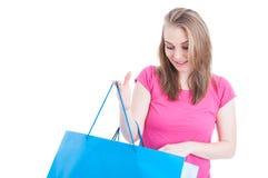 Härlig le kvinnlig som ser in i hennes shoppingpåse Arkivbilder