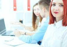 Härlig le kvinnlig student medan par hennes kollegor som arbetar i bakgrund Arkivfoton