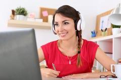 Härlig le kvinnlig student som använder online-utbildningsservice royaltyfria bilder