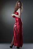 Härlig le modell som poserar i lång skinande klänning arkivfoton