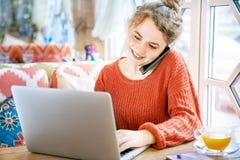 Härlig le rödhårig fräknig flicka som arbetar med bärbara datorn på tabellrestaurangen under en konversation på telefonen arkivbild