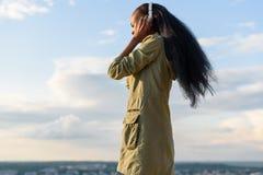 Härlig le svart afrikansk amerikankvinna för barn med långt hår som lyssnar till musik Suddig cityscape på bakgrund Royaltyfri Foto
