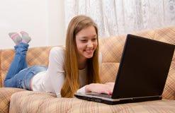 Tonårs- flicka på sängen med anteckningsboken Royaltyfria Foton