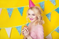 Härlig le ung blond kvinna med en kaka Beröm och parti Royaltyfri Fotografi
