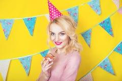 Härlig le ung blond kvinna med en kaka Beröm och parti Royaltyfria Foton