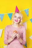 Härlig le ung blond kvinna med en kaka Beröm och parti Arkivbild