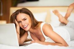 Härlig le ung brunettkvinna för stående som lägger i säng som kopplar av genom att använda bärbar datordatoren Arkivbilder