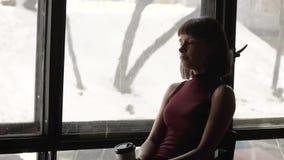 Härlig ledsen flicka vid fönstret hemma arkivfilmer