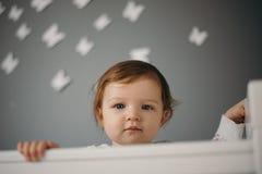 Härlig ledsen stående för liten flicka inomhus i rum för barn` s Royaltyfri Foto