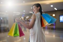 Härlig leendeflicka som rymmer den färgrika shoppingpåsen Arkivbild