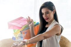 Härlig leendeflicka som rymmer den färgrika shoppingpåsen Arkivfoton