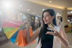 Härlig leendeflicka som rymmer den färgrika shoppingpåsen Royaltyfri Fotografi