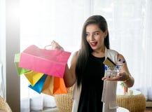 Härlig leendeflicka som rymmer den färgrika shoppingpåsen Royaltyfria Bilder
