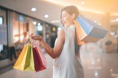 Härlig leendeflicka som rymmer den färgrika shoppingpåsen Arkivfoto