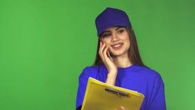 Härlig leveranskvinna som talar på telefonen som rymmer en skrivplatta stock video