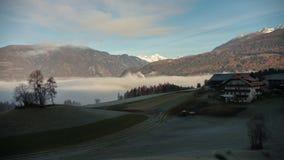 härlig liggande Gröna fält och berg som fylls med träd Låga vita moln Timelapse stock video