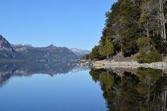 härlig liggande sol, sjöar och mountainss Arkivbild