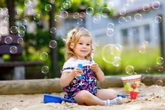 Härlig liten blond litet barnflicka som har gyckel med att blåsa såpbubblablåsaren Gulligt förtjusande behandla som ett barn barn royaltyfri bild
