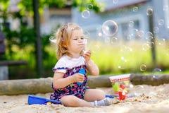 Härlig liten blond litet barnflicka som har gyckel med att blåsa såpbubblablåsaren Gulligt förtjusande behandla som ett barn barn arkivfoto